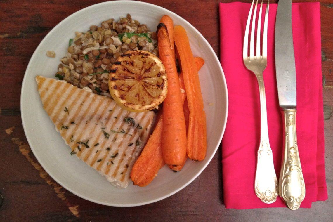 Bord met gegrilde zwaardvis, citroen, romige linzen worteltjes uit de oven